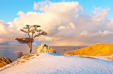 Baikal Lake in December at sunset. Olkhon Island. Multi-colored ribbons are tied on Wish Tree, snowy clouds are over the Small Sea Strait. Magnificent winter landscape, natural background