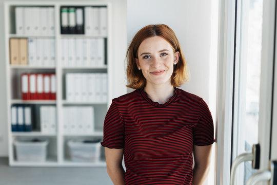 Smiling businesswoman standing at the office door