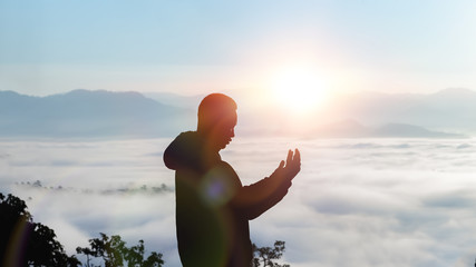 Man hands praying in morning with sunlight on mountain. christian silhouette concept. Wall mural