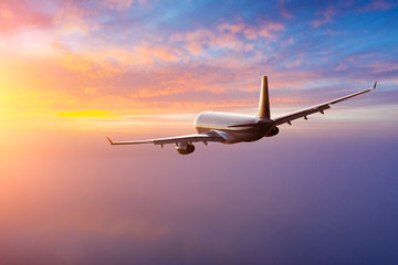 Passengers commercial airplane flying above clouds in sunset light. Concept of fast travel,...