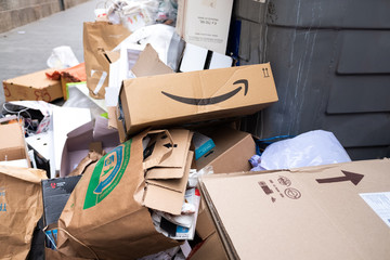 Amazon Prime cardboard box thrown into a pile of trash from a full dumpster.