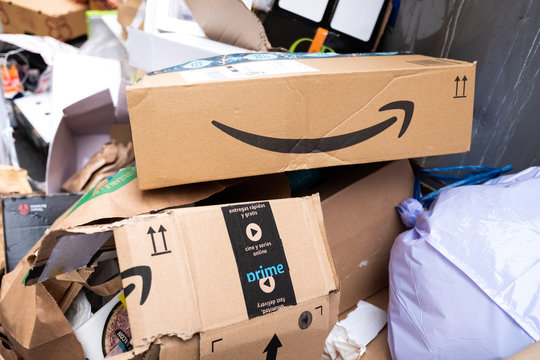 Amazon Prime cardboard box thrown in the trash in a pile of rubbish on the street after Black Friday
