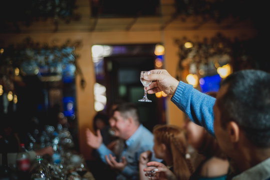 A man raises a glass of vodka for a toast