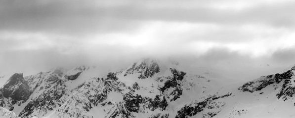 Fototapete - Snowy mountains in haze and storm clouds