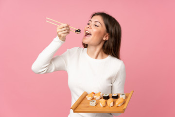 Fotobehang Sushi bar Young girl with sushi over isolated pink background