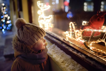 Little boy admires Christmas decorations in showcase of shop on winter evening. Tourist looking on...