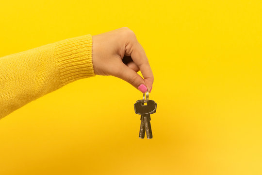 female hand holding house keys, suggesting, over yellow background