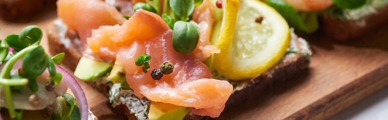 panoramic shot of salmon fillet near sliced lemon on tasty smorrebrod sandwich Wall mural