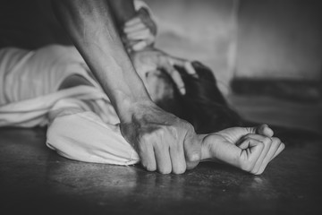 Close up of man hands holding a woman hands for rape and sexual abuse. black and white picture.