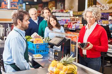 Seniorin beim Bezahlen an der Kasse im Supermarkt