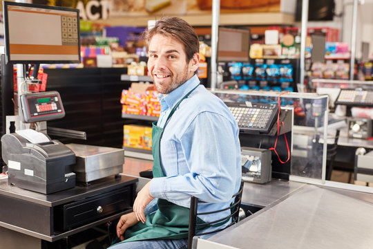 Mann als Kassierer sitzt an der Registrierkasse