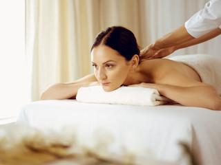 Pretty brunette woman enjoying procedure of back massage in spa salon. Beauty concept