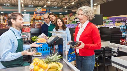 Alte Frau sucht Geld an Kasse vom Supermarkt