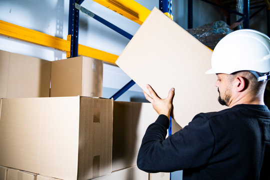 Warehouse worker. Man with a hard hat placing a carton box on a pile on a storage shelf.
