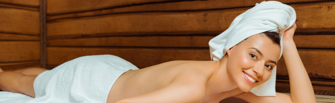 panoramic shot of attractive and smiling woman in towels lying in sauna