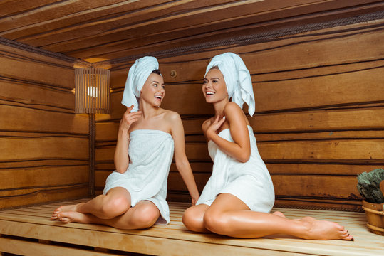 smiling and attractive friends in towels talking in sauna