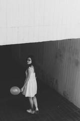 Black and white shot of Portrait of young woman with red balloon in hand standing against tunnel . Scary movie concept.