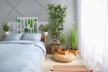 Big comfortable bed and plants in interior of room