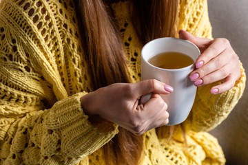 cropped view of woman in yellow sweater holding cup of tea
