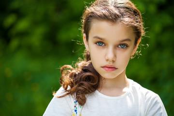 Calm brunette little girl in summer park
