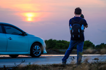 Tourists take pictures of the sunset with his car.