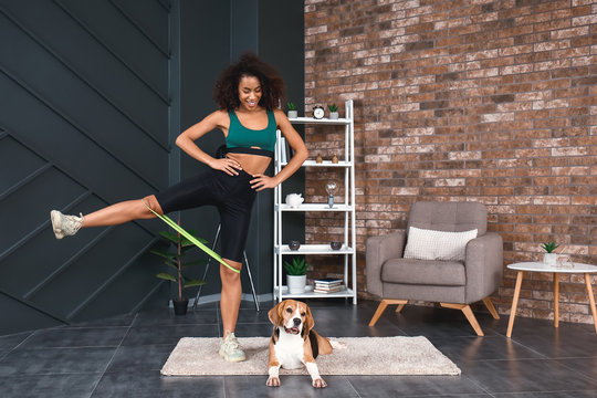 Sporty African-American woman with cute dog training at home