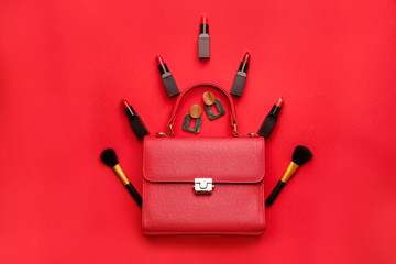 Beautiful Christmas tree made of lipsticks, brushes and earrings and bag on color background