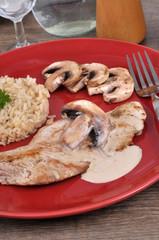 Escalope de veau avec du riz et une sauce aux champignons dans une assiette