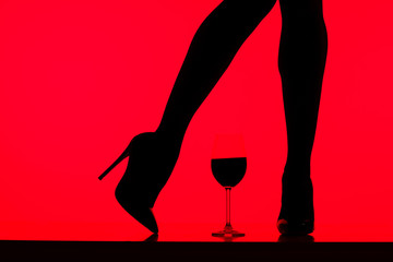 cropped view of black silhouette of girl in heels with glass of wine isolated on red