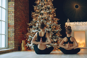 Group yoga class. Woman and child doing yoga at christmas.