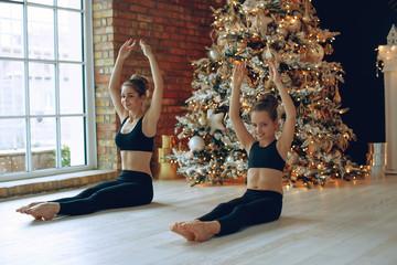 Group yoga class. Woman and child doing yoga at christmas.