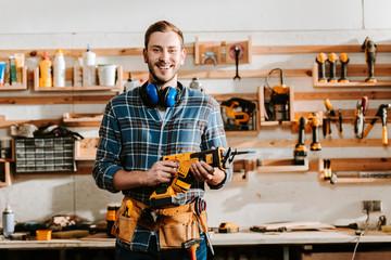 Fototapeta happy bearded carpenter holding hammer drill in workshop obraz