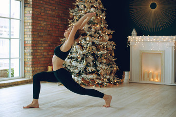 Beautiful woman practices yoga in christmas.