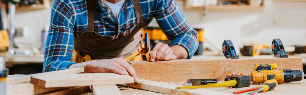 panoramic shot of carpenter touching wooden dowel