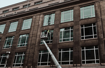 worker cleaning the windows of a building with a crane -