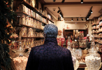 elegant trendy mature woman with short hair looking at a shop window of a sweet shop during the christmas holidays-