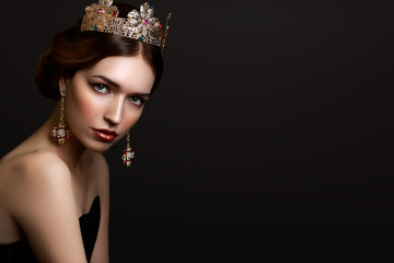 Close-up portrait beautiful girl with red lipstick in golden crown and earrings on dark background