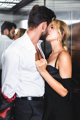 Businessman taking off jacket while kissing sexy woman in office elevator