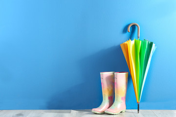 Wall Mural - Beautiful colorful umbrella and rubber boots near blue wall. Space for text