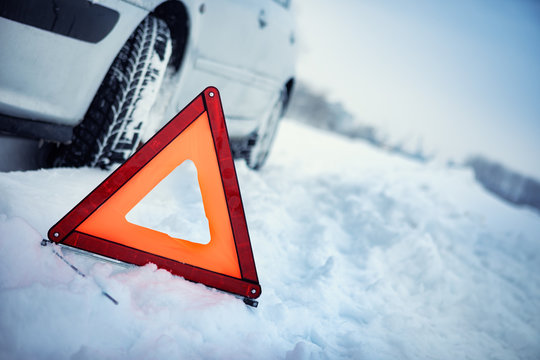 Close up of red warning triangle with a broken down car in winter