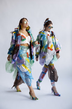 Women wearing plastic on white background. Female model in clothes and shoes made of garbage. Fashion, style, recycling, eco and environmental concept. Too much pollution, we're eating and taking it.