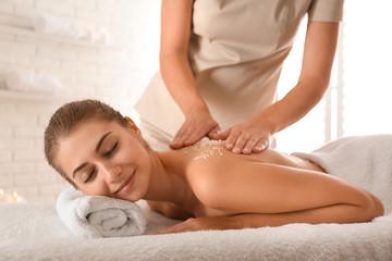 Young woman having body scrubbing procedure with sea salt in spa salon