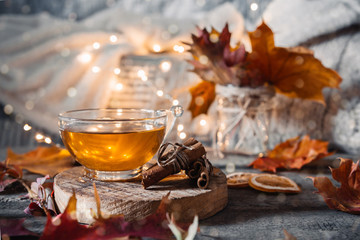 Cozy autumn or winter at home. A cup of tea, autumn casts a book a garland on a wooden table near a bed with warm plaids. Lifestyle autumn hygge lagom?concept of a holiday and autumn weekend.