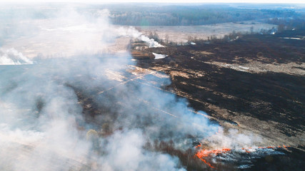 Forest and field fire. Dry grass burns, natural disaster. Aerial view. Smooth flight over the place of fire, a small stream blocks the path to the fire.