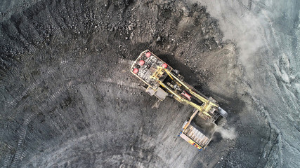 Cable excavator loads overburden from the body of a mining truck.