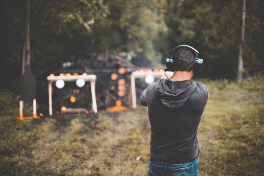 Shallow focus shot of a male shotting a gun at the gun range