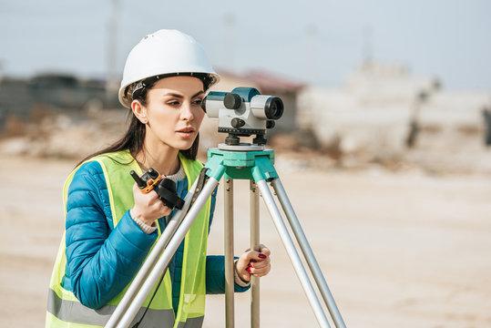 Female surveyor with radio set looking through digital level