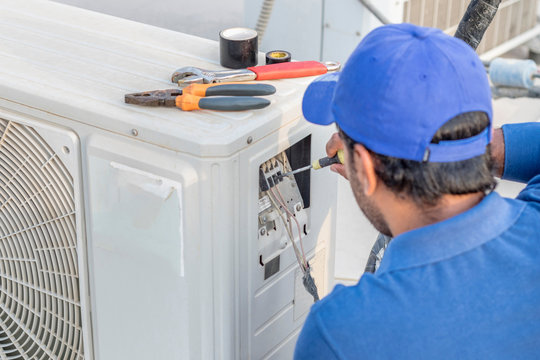a professional electrician man is fixing a heavy duty unit of central air conditioning system by his tools on the roof top and wearing  uniform and white cap