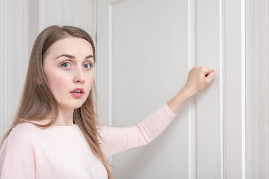 Afraid woman knocks on the door, girl came to visit, portrait, close up