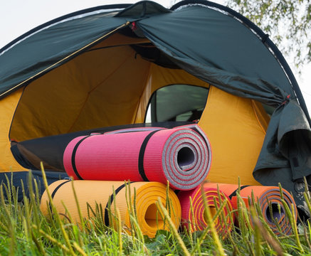 Open tent and rolled sleeping pads.